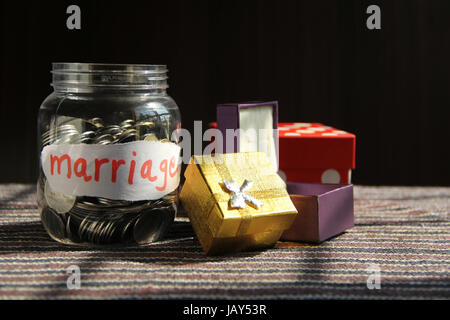 Coins in money jar with marriage label, finance concept - Stock Photo