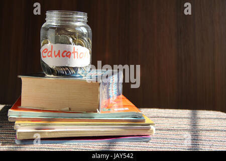 Coins in money jar with education label, finance concept - Stock Photo