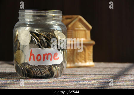 Coins in money jar with home label, finance concept - Stock Photo