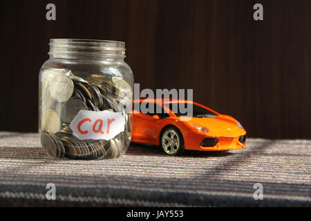 Coins in money jar with car label, finance concept - Stock Photo