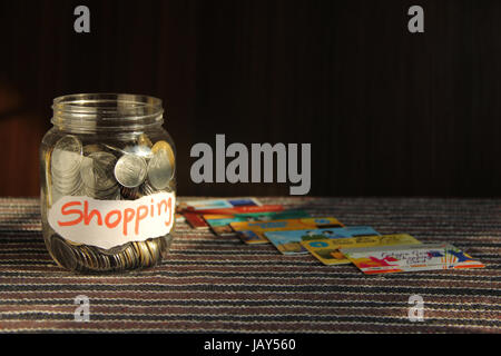 Coins in money jar with shopping label and credit cards, finance concept - Stock Photo