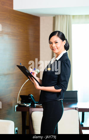 Asian Chinese Housekeeping manager or assistant controlling or checking the room or suit of a hotel with a checklist - Stock Photo