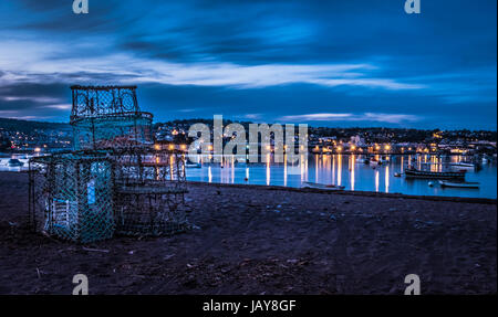 Boats on the red sanded beach at Shaldon in Devon at night. - Stock Photo