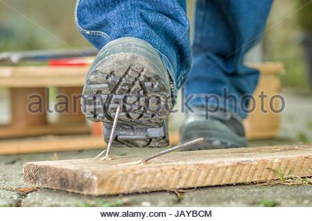 Arbeiter mit Sicherheitsschuhen tritt in einen Nagel - Stock Photo