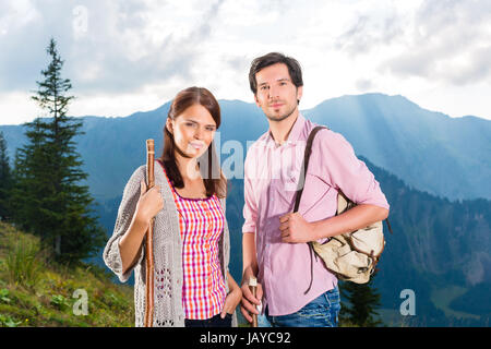 Hiking - Young couple standing on mountain summit in the Bavarian Alps enjoying the panorama in their leisure time - Stock Photo