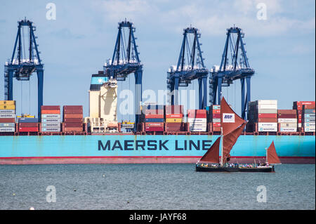 Thames barge sailing past Maersk Line container ship, Felixstowe container port, seen from Harwich Essex England - Stock Photo