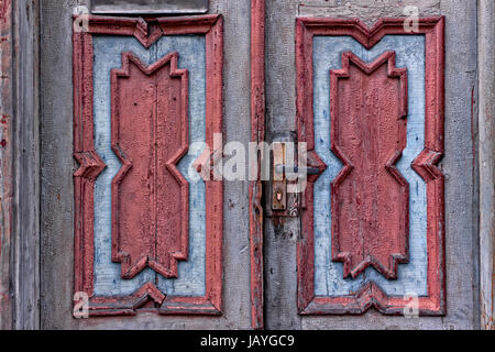 Beautifully carved patterns on an old door in Tallinn, Estonia. The doors seem to be in a bad shape. - Stock Photo