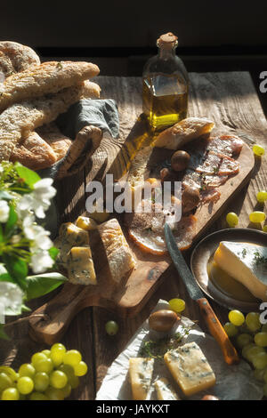Homemade bread, cheese, olives, jamon and flowers on old boards vertical - Stock Photo