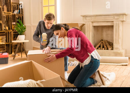 side view of young couple packing things for moving home - Stock Photo