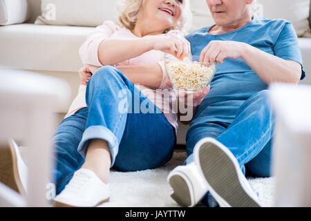 Cropped shot of happy senior couple eating popcorn on sofa - Stock Photo