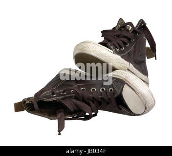 a pair of old brown sneakers in white back - Stock Photo