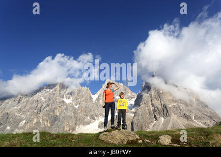 Mother and son standing on a rock and enjoying the view, Baita Segantini, Dolomites, Italy. - Stock Photo