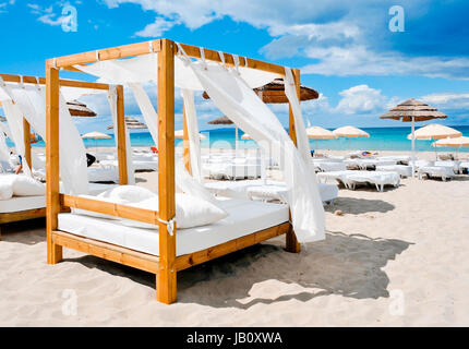 view of some beds in a beach club in a white sand beach in Ibiza, Spain - Stock Photo