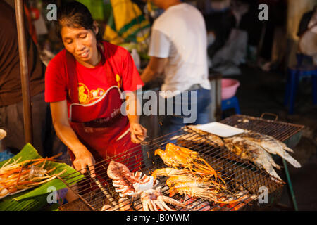 CHIANG MAI, THAILAND - AUGUST 27: Woman cooks prawns and squids on the grill at the Sunday Market (Walking Street) - Stock Photo
