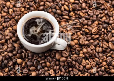 cup of steaming coffee on bunch of roasted coffee beans - Stock Photo