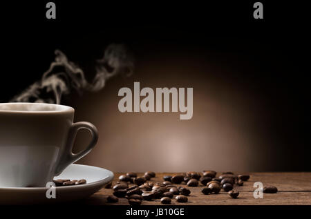 cup of steaming coffee on wooden table with roasted coffee beans. - Stock Photo