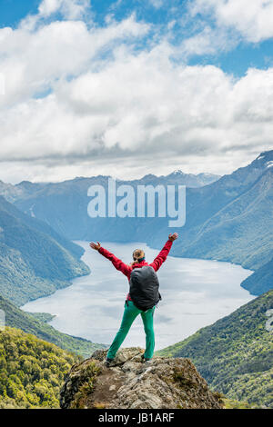 Female hiker is looking at the South Fiord of Lake Te Anau, stretching arms in the air, at back the Southern Alps - Stock Photo