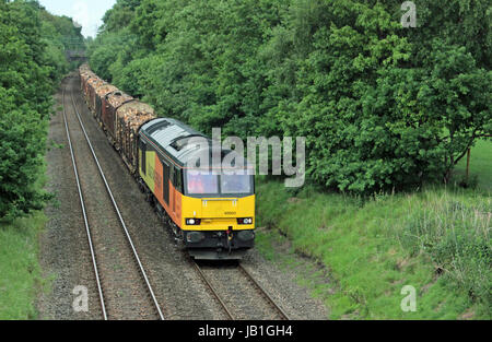 A Colas diesel locomotive passing through Moore pulling a train loaded with logs that are destined for the chip - Stock Photo