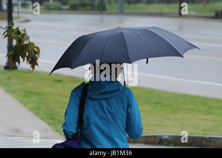 Woman wearing blue raincoat covering her head with an umbrella - Stock Photo
