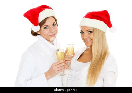 Two young pretty women in Santa Claus cap and winter clothes with glasses of champagne  on a white background. - Stock Photo