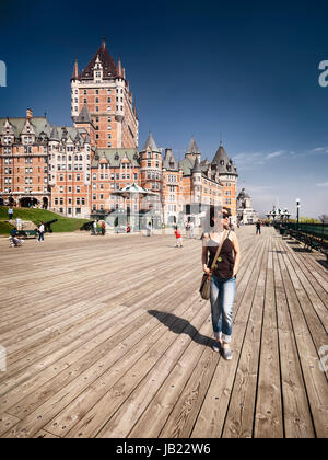 Young woman walking alone on Dufferin terrace boarwalk with Fairmont Le Château Frontenac castle in the background, - Stock Photo
