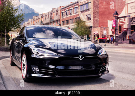 Black 2017 Tesla Model S luxury electric car parked on a city street in Banff, Alberta, Canada. - Stock Photo