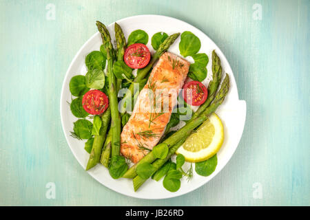 An overhead photo of a plate of grilled salmon with green asparagus, cherry tomatoes, corn salad, and a slice of - Stock Photo