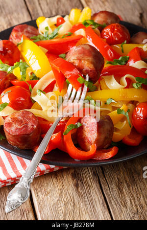 Fettuccine pasta with bell pepper, grilled sausages and tomato close-up on a plate. vertical - Stock Photo