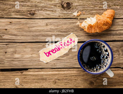 Breakfast - a handwritten note on a small fragment of torn paper lying alongside an aromatic cup of frothy full - Stock Photo