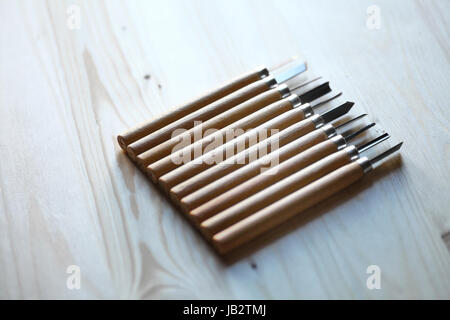 A set of wood sculpture tools on a wood plank. - Stock Photo