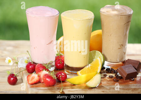Three delicious smoothies with yoghurt or ice cream blend, two made with fruit and one of chocolate, together with - Stock Photo