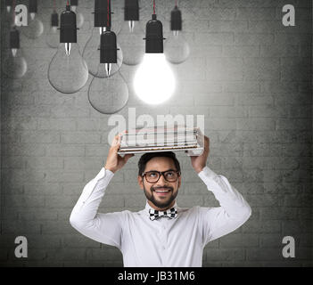 Businessman with book and glowing light bulb - Stock Photo