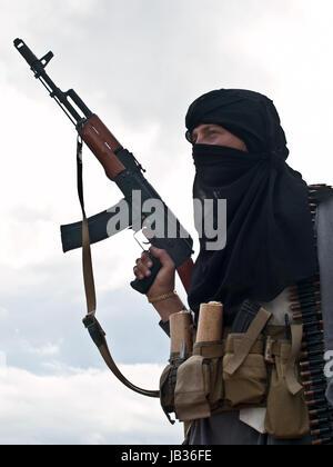 Muslim rebel with rifle - Stock Photo