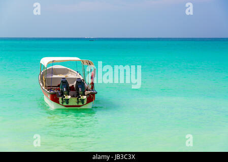 Turquoise Caribbean water as seen from Playa Blanca near Cartagena Colombia with a boat in the foreground - Stock Photo
