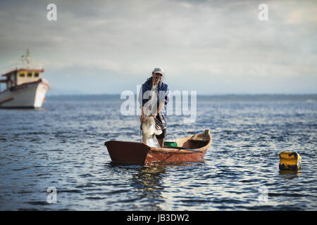 Pontal do Sul, Paraná, Brazil - June 3, 2017: Fisherman on his boat fishing alone. - Stock Photo