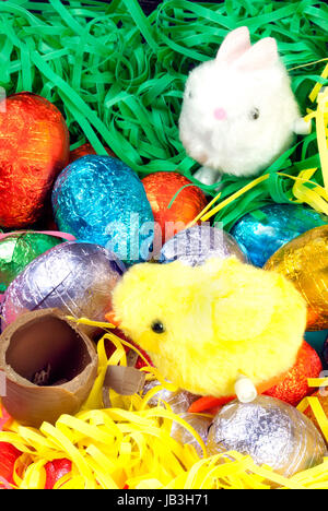 Close-up of a fluffy yellow chick racing a fluffy white bunny over a pile of colorful eggs and grasses to a chocolate - Stock Photo