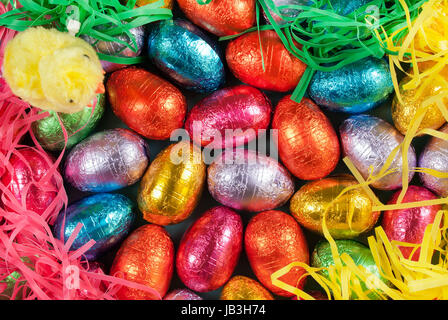 Close-up of pile of colorful chocolate Easter eggs surrounded by colorful grasses with a fluffy yellow chick toy - Stock Photo
