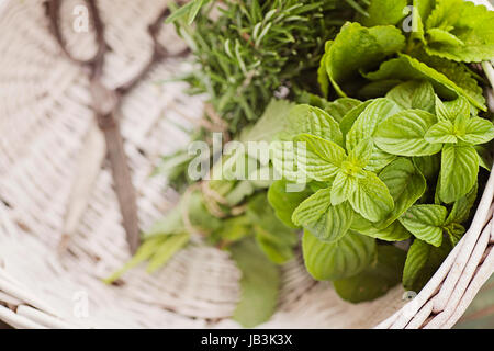 Fresh herbs. Melissa, rosemary and mint in rustic setting - Stock Photo