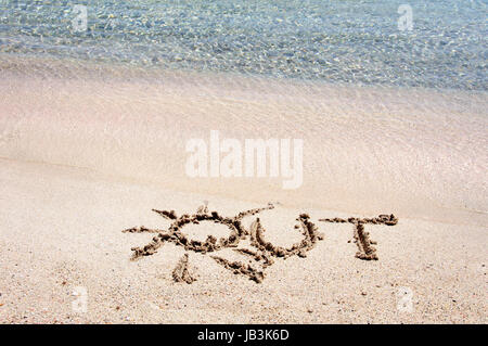 Word 'OUT' written on sand on a beautiful beach, blue waves in background - Stock Photo