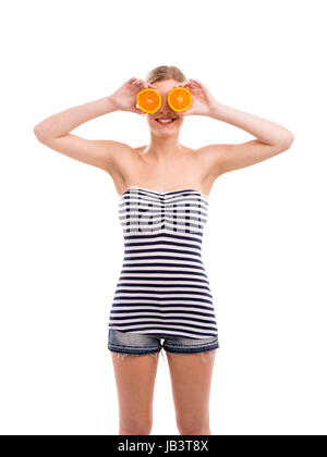 Beautiful woman holding orange slices in front of her eyes - Stock Photo