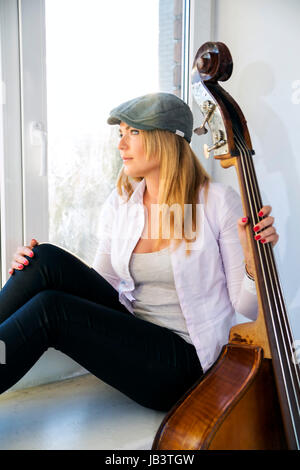 Charming woman with contrabas thinking about something seriously - Stock Photo