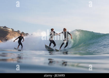 Overcrowded waves in Southern California lead two surfers to engage in a fistfight while surfing at Black's Beach. - Stock Photo