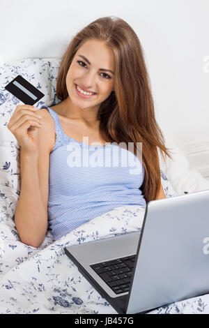 junge glückliche frau mit kreditkarte beim online shopping im bett zuhause - Stock Photo