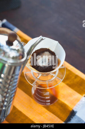 Pour Over Coffee Drip Brewing with paper filter while coffee blooming - Stock Photo