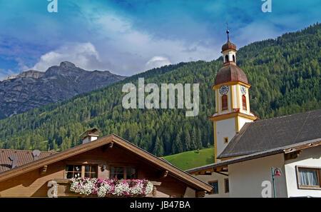 Die Serles und der Kirchturm von Neustift im Stubaital in Tirol; im Vordergrund Blumen an einem Balkon The Serles - Stock Photo