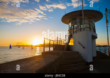 Mount Batten pier by sea ocean going off into distance at golden sunset with sailing yachts in Plymouth Sound, Devon, - Stock Photo