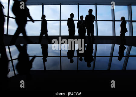 Three white collar workers communicating in office against window with several business partners walking around - Stock Photo