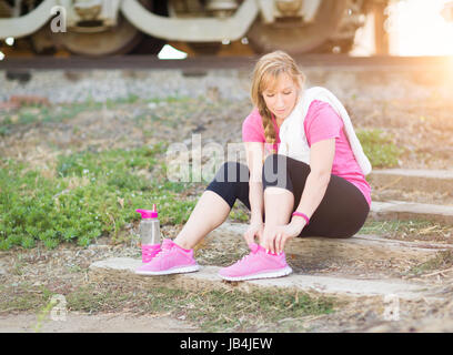 Young Adult Woman Outdoors With Towel and Water Bottle Tying Her Shoe Ready for Workout. - Stock Photo