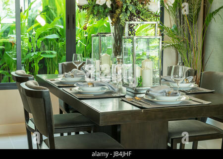 table set on wooden table and chairs in tropical dinning room - Stock Photo