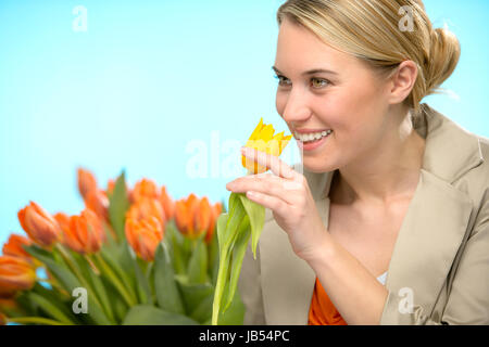 Woman smelling one yellow tulip spring flowers smiling - Stock Photo
